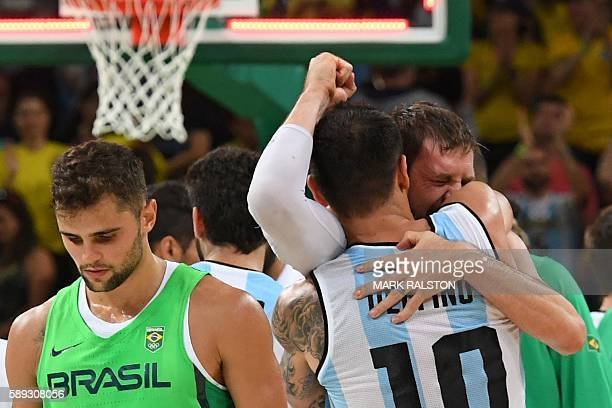 Argentina's shooting guard Carlos Delfino embraces Argentina's small forward Andres Nocioni as Brazil's point guard Raulzinho Neto walks by after...