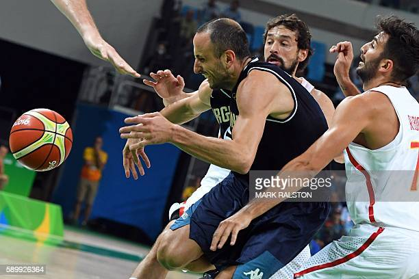 Argentina's shooting guard Manu Ginobili is sandwiched between Spain's guard Sergio Llull and Spain's point guard Ricky Rubio during a Men's round...