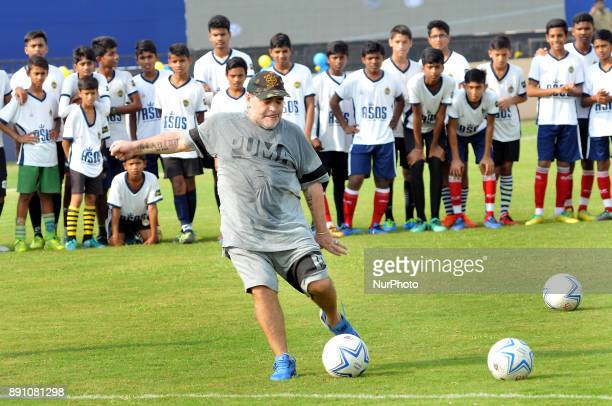 Argentina's soccer legend Diego Maradona kicks a football gestures during a football workshop with school students in Barasat around 38 Km north of...
