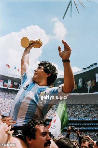 Argentina's soccer star team captain Diego Maradona brandishes the World Soccer Cup won by his team after a 3-2 victory over West Germany on June 29,...
