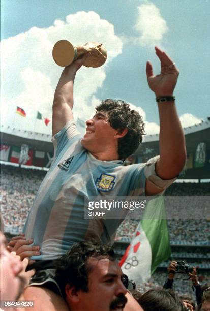 Argentina's soccer star team captain Diego Maradona brandishes the World Cup won by his team after a 3-2 victory over West Germany 29 June 1986 at...
