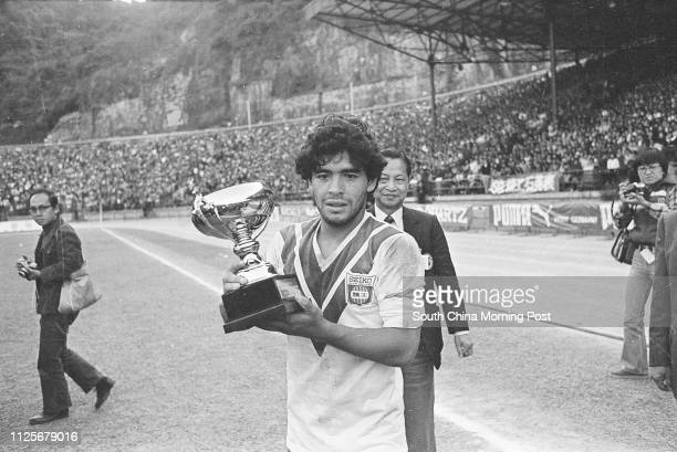 Argentina's soccer superstar Diego Maradona clad in a jersey of Hong Kongbased Seiko soccer team holds a trophy after his team Boca Juniors won Seiko...