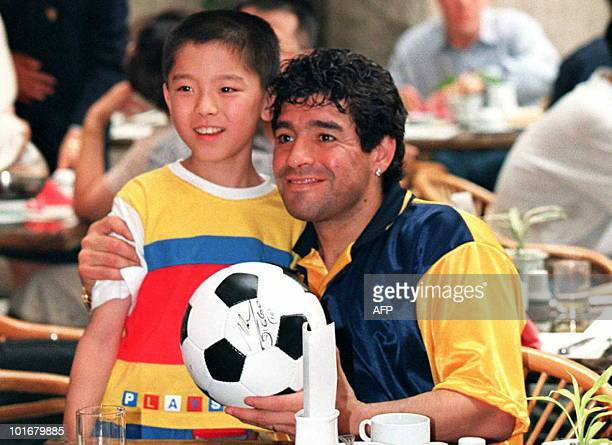 Argentina's soccer superstar Diego Maradona poses with a young Chinese boy after autographing a ball at a hotel in Beijing 22 July Maradona and his...