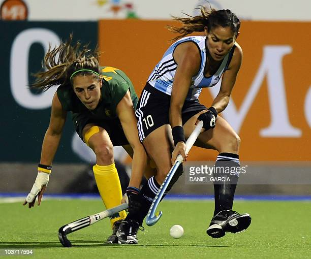 Argentina's Soledad Garcia dribbles past South Africa's LisaMarie Deetlefs during the field hockey Group B match for the Women World Cup 2010 in...