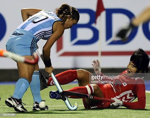 Argentina's Soledad Garcia vies for the ball with Korea's captain Lee Seon Ok during the Women World Cup 2010 field hockey Group B match in Rosario...