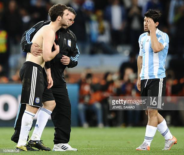 Argentina's striker Gonzalo Higuain is comforted by a trainer as Argentina's striker Sergio Aguero walks past after the quarter final 2010 World Cup...