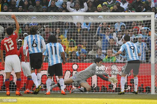 Argentina's striker Gonzalo Higuain watches as his header sails past South Korea's midfielder Ki SungYueng and into the goal during their Group B...