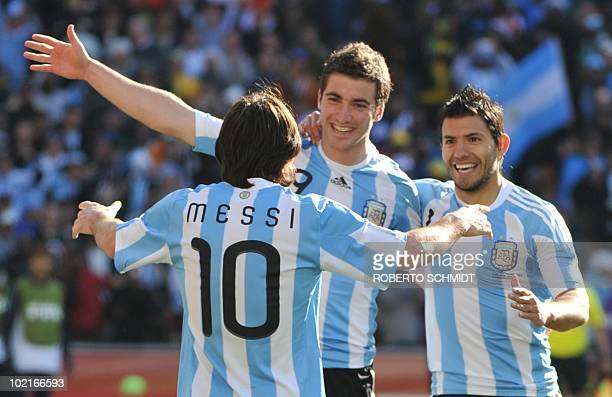 Argentina's striker Lionel Messi celebrates with Argentina's striker Gonzalo Higuain and Argentina's striker Sergio Aguero after Higuain scored his...