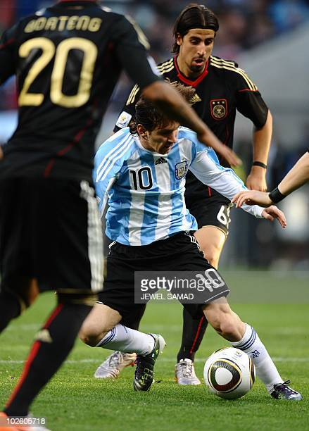 Argentina's striker Lionel Messi fights for the ball with Germany's defender Jerome Boateng and Germany's midfielder Sami Khedira during the quarter...