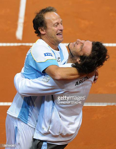 Argentina's team captain Martin Jaite and player Juan Monaco celebrate after the doubles Davis Cup match victory of Argentinian Eduardo Schwank and...