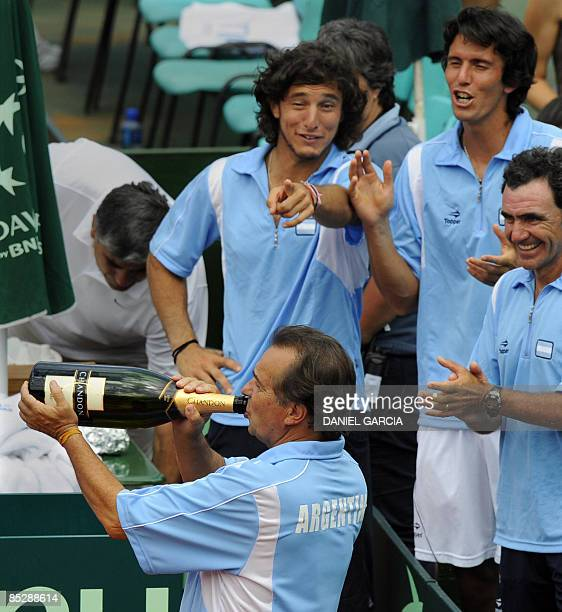 Argentina's team captain Modesto Vazquez drinks champagne as players Juan Monaco and Juan Ignacio Chela and deputy team captain Ricardo Rivera look...