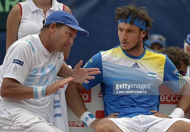Argentina's tennis captain Martin Jaite talks to Argentina's tennis player Juan Monaco during their Davis Cup World Group 1st Round single tennis...