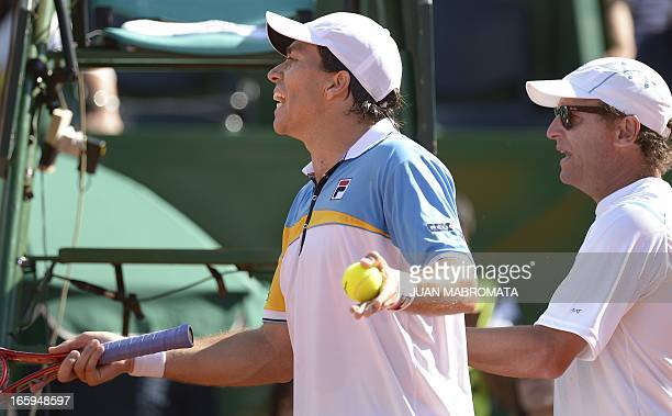 Argentina's tennis player Carlos Berlocq and team captain Martin Jaite gesture during their 2013 Davis Cup World Group quarterfinal singles tennis...