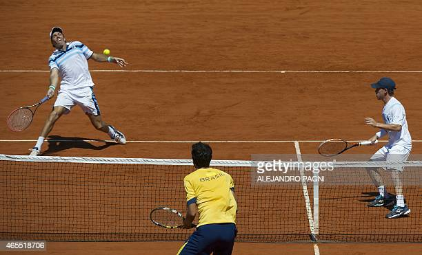 Argentina's tennis player Carlos Berlocq returns the ball to Brazil's tennis player Marcelo Melo and Bruno Soares next to teammate Diego Schwartzman...