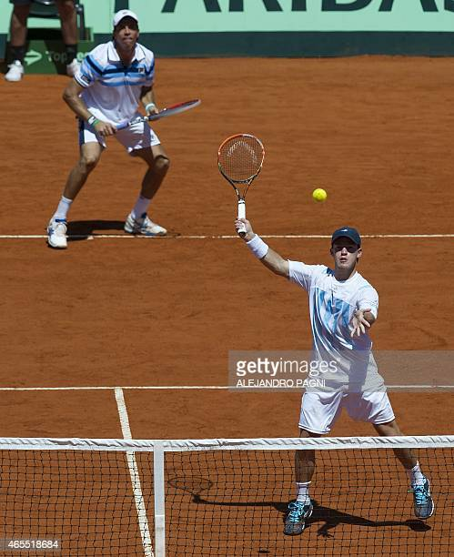 Argentina's tennis player Diego Schwartzman returns the ball to Brazil's tennis player Marcelo Melo and Bruno Soares next to teammate Carlos Berlocq...