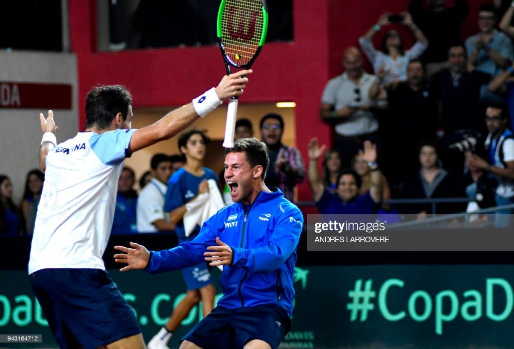 Argentina's tennis player Guido Pella (L) celebraters with teammate Diego Schwartzman after defeating Chile's Christian Garin during their 2018 Davis Cup Americas Group second round single tennis match at Aldo Cantoni stadium in San Juan, Argentina on April 7, 2018. / AFP PHOTO / Andres Larrovere