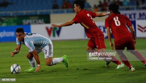 Argentina's U20 Martinez Lautaro Javier fights for the ball with Vietnam's U22 Hoang Van Khanh during a friendly football match at Hanoi's My Dinh...
