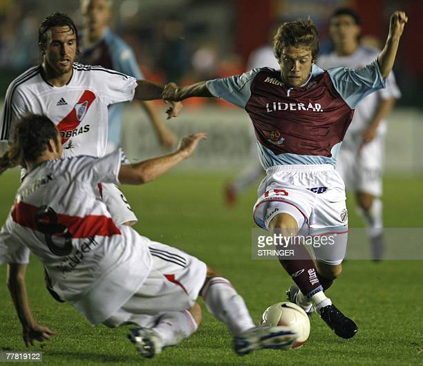 Argentine Arsenal's midfielder Alejandro Gomez vies for the ball with Fernando Belluschi and Oscar Ahumada of River Plate during their Copa...