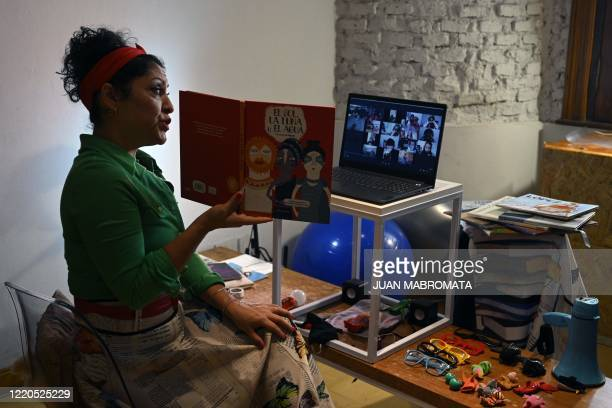 """Argentine artist Any Gonzalez of """"La Llave Producciones Artisticas"""" reads a book at her m home in Buenos Aires on June 9 during a birthday party..."""