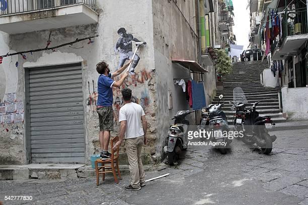 Argentine artist Santiago Spiga alias 'Spiga' attaches a mural of Argentine former football player Diego Armando Maradona to celebrate the 30th...