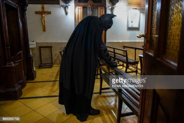 Argentine Batman, prays in a chapel at the 'Sor Maria Ludovica' children's Hospital in La Plata, 60 kilometres south of Buenos Aires, on June 2,...