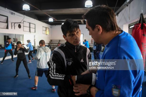 Argentine boxer Brian Arregui listens to his coach Mariano Carrera during a training session in Buenos Aires on October 01 2018 Arregui who started...