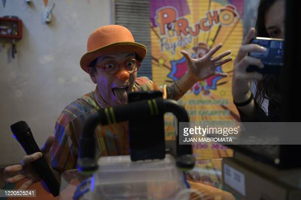 Argentine clown Gabriel Valino , known as 'Payaso Pirucho', performs next to his neighbour and assistant Guillola at her home on June 6 during a...