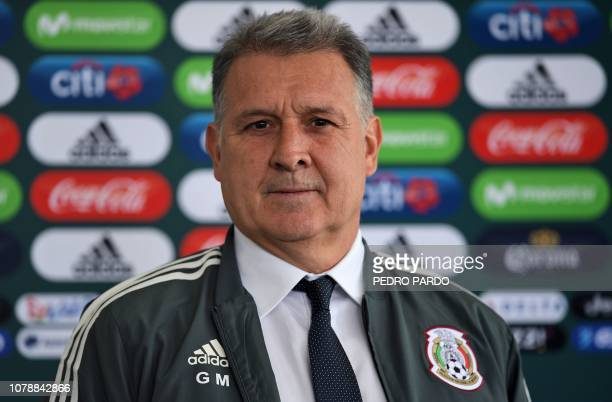 Argentine coach Gerardo 'Tata' Martino poses with a training jacket of the Mexican national football team during his presentation as new coach of the...