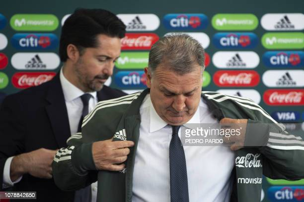 Argentine coach Gerardo 'Tata' Martino puts the training jacket of the Mexican national football team as the president of the Mexican Football...