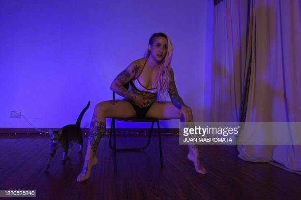 Argentine dancer Natasha Szuka, teaches sexy chair dance next to her cat 'Lara', at her home in Buenos Aires on June 9 during a party celebrated...
