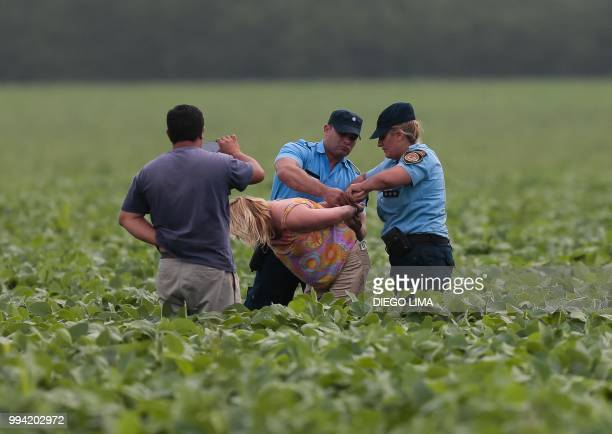 Argentine environmentalist Sofia Gatica is arrested by police officers as a farmer records the action on video after she tried to stop the spraying...