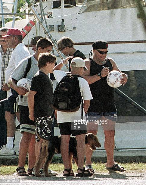 Argentine exsoccer player Diego Armando Maradona signs a ball with children 30 January 2000 at Hemingway Marina in Havana where he is undergoing drug...