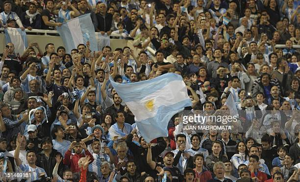 Argentine fans cheer for their team during a Brazil 2014 World Cup South American qualifier match against Paraguay at Mario Kempes stadium in Cordoba...