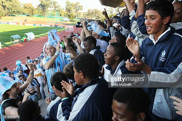 Argentine fans teach a group of local school children a football chant while waiting for Argentina's national football team to take the field during...