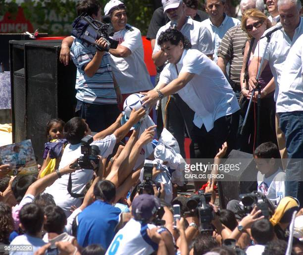 Argentine football legend and national team head coach Diego Maradona is handed a ball to autograph at a public act in the humble neighbourhood where...