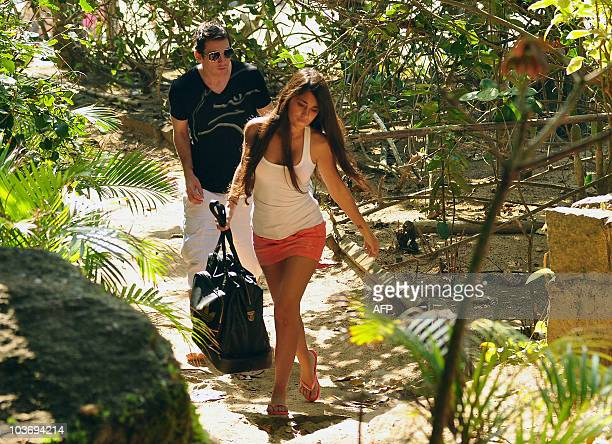 Argentine football star and player of Spain's Barcelona FC Lionel Messi and his girlfriend Antonella Roccuzzo leave the beach after the arrival of...