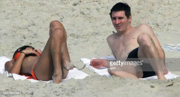 Argentine football star and player of Spain's Barcelona FC Lionel Messi sunbathes with his girlfriend Antonella Roccuzzo in a beach in Rio de Janeiro...