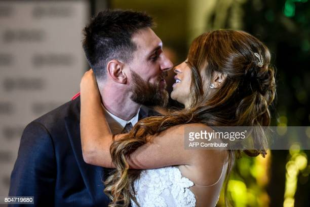 TOPSHOT Argentine football star Lionel Messi and bride Antonella Roccuzzo pose for photographers during their wedding at the City Centre Complex in...