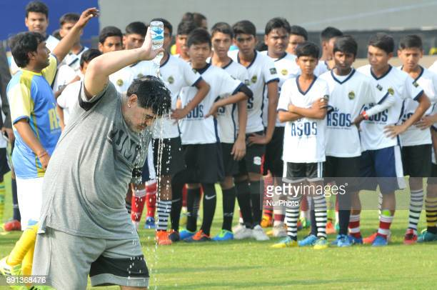 Argentine footballer Diego Maradona gestures as students looks on during a football workshop in Barasat around 38 Km north of Kolkata on December 12...
