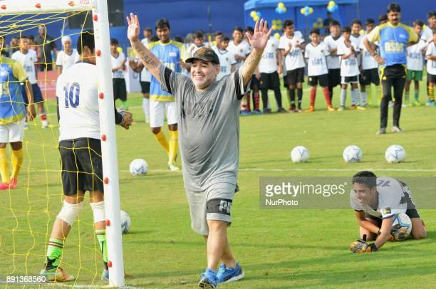Argentine footballer Diego Maradona gestures during a football workshop with school students in Barasat around 35 Km north of Kolkata on December 12...