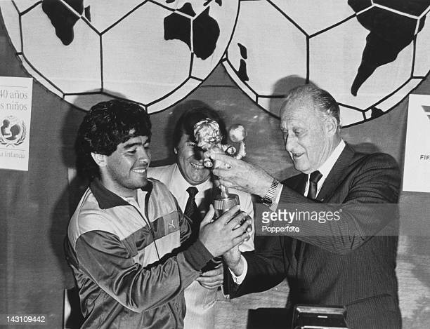 Argentine footballer Diego Maradona receives the FIFA Fair Play Trophy on behalf of the Argentine national team from FIFA President Joao Havelange...