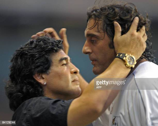 Argentine former football legend Diego Maradona greets former Uruguay's footballer Enzo Francescoli during the friendly match called 'To the Playing...