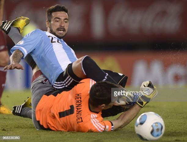 Argentine forward Ezequiel Lavezzi clashes with Venezuelan goalkeeper Daniel Hernandez during a Brazil 2014 World Cup South American qualifier...