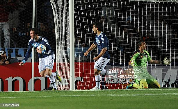 Argentine forward Gonzalo Higuain celebrates near teammate Sergio Aguero after scoring past Uruguayan goalkeeper Fernando Muslera during their 2011...