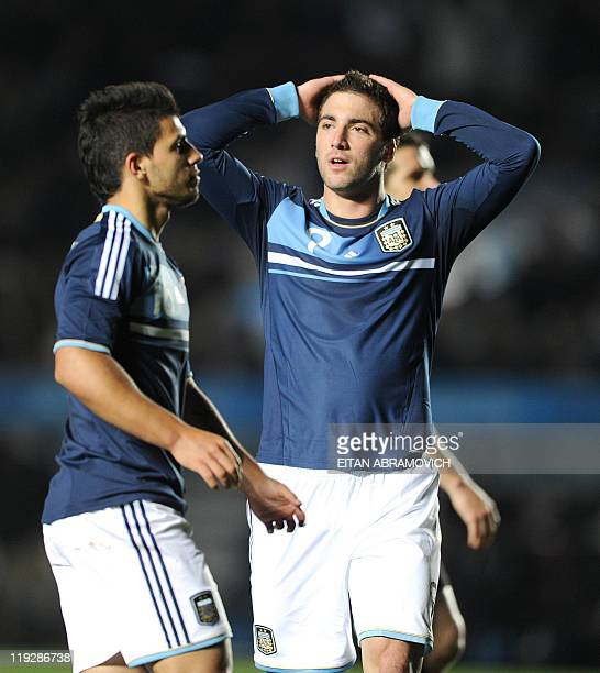 Argentine forward Gonzalo Higuain gestures next to teammate Sergio Aguero after missing a goal during their 2011 Copa America quarterfinal football...