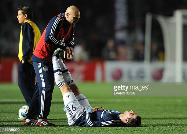 Argentine forward Gonzalo Higuain stretches with midfielder Esteban Cambiasso before the extratime of their 2011 Copa America quarterfinal football...