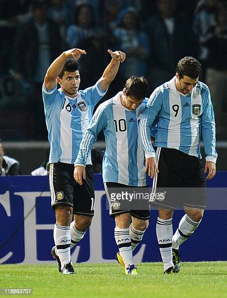 Argentine forward Sergio Aguero gestures to teammate Lionel Messi alongside forward Gonzalo Higuain after celebrating their second goal against Costa...
