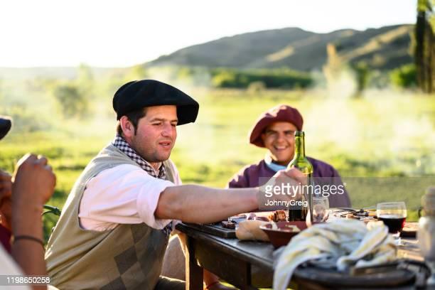 argentinska gauchos i traditionella kläder njuter asado - argentina bildbanksfoton och bilder