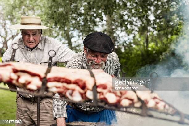 """argentine gauchos preparing a """"costillar"""" (rib) - argentina traditional clothing stock photos and pictures"""