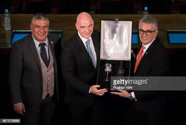 Argentine goldsmith Carlos Pallarols gives a box with a glass and a bottle of wine to Gianni Infantino president of FIFA as Claudio Chiqui Tapia...